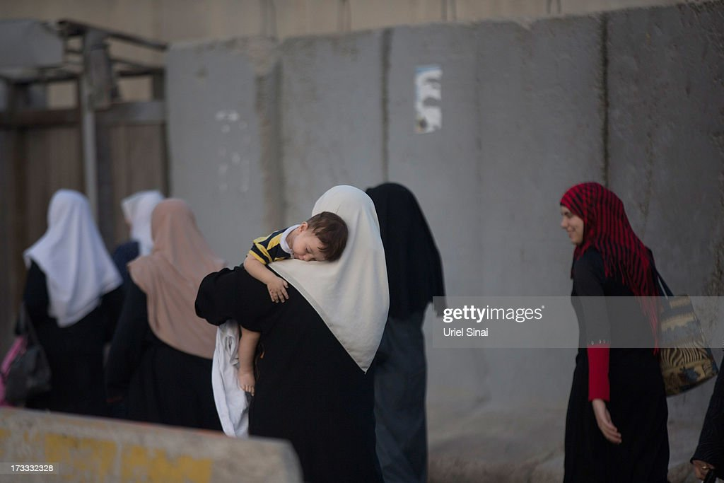 A Palestinian Muslim woman carries her baby as worshippers cross the Qalandia checkpoint on their way to Jerusalem on July 12, 2013 near Ramallah, West Bank. Thousands of Palestinian worshippers crossed from the West Bank into Israel to attend the first Friday prayers of Ramadan at the the Al-Aqsa mosque compound in Jerusalem.