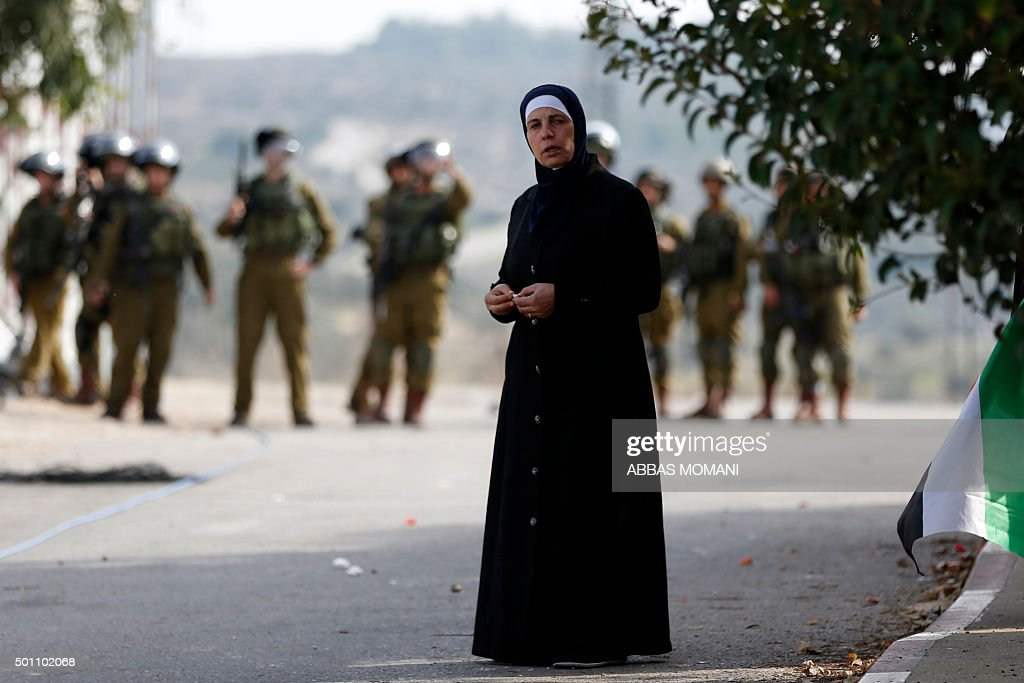 A Palestinian Muslim woman stands between Palestinian protesters and Israeli soldiers during clashes on December 12 2015 in the village of Abud...