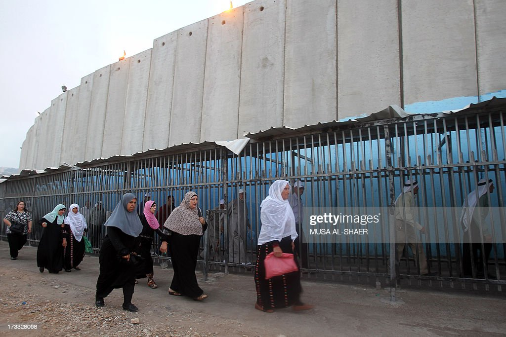 Palestinian Muslim women walk past Israel's controversial separation barrier on the outskirts of the West Bank town of Bethlehem on July 12, 2013 on their way to Jerusalem to attend the Friday prayers at the Al-Aqsa mosque during the Muslim fasting month of Ramadan.