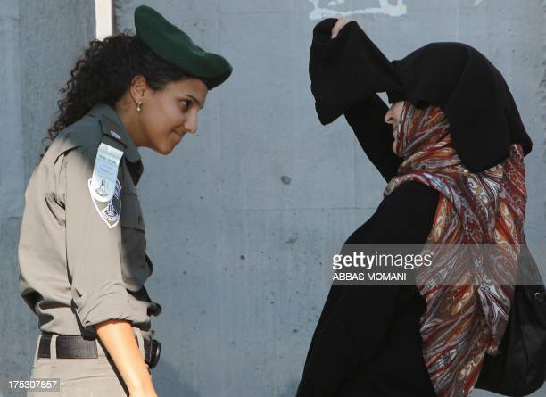 A Palestinian Muslim worshiper lifts her veil to show her face to an Israeli border guard as she crosses the Qalandia checkpoint between Ramallah and...