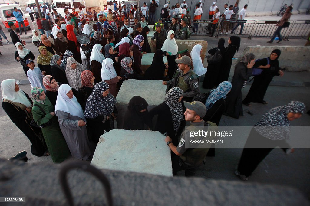 Palestinian Muslim worshipers cross the Qalandia checkpoint between Ramallah and Jerusalem on their way to attend the first Friday prayers of Ramadan in the Al-Aqsa mosque compound on July 12, 2013.