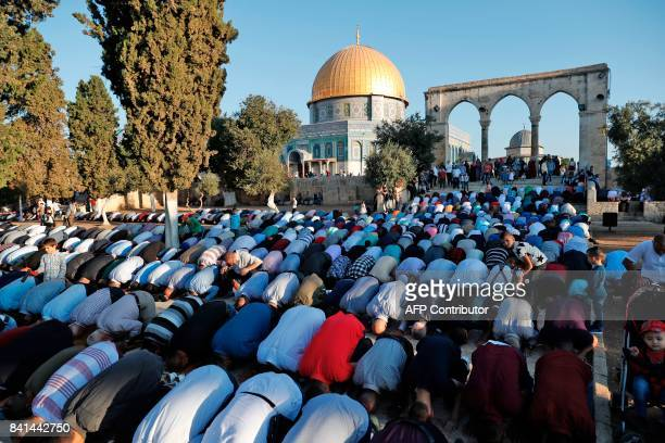 Palestinian Muslim worshipers pray on the morning of the first day of Eid alAdha near the Dome of Rock mosque inside the alAqsa Mosque compound...
