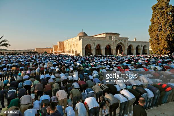 Palestinian Muslim worshipers pray outside alAqsa Mosque in Jerusalem's old city on the first day of Eid alAdha on September 1 2017 Eid alAdha is...