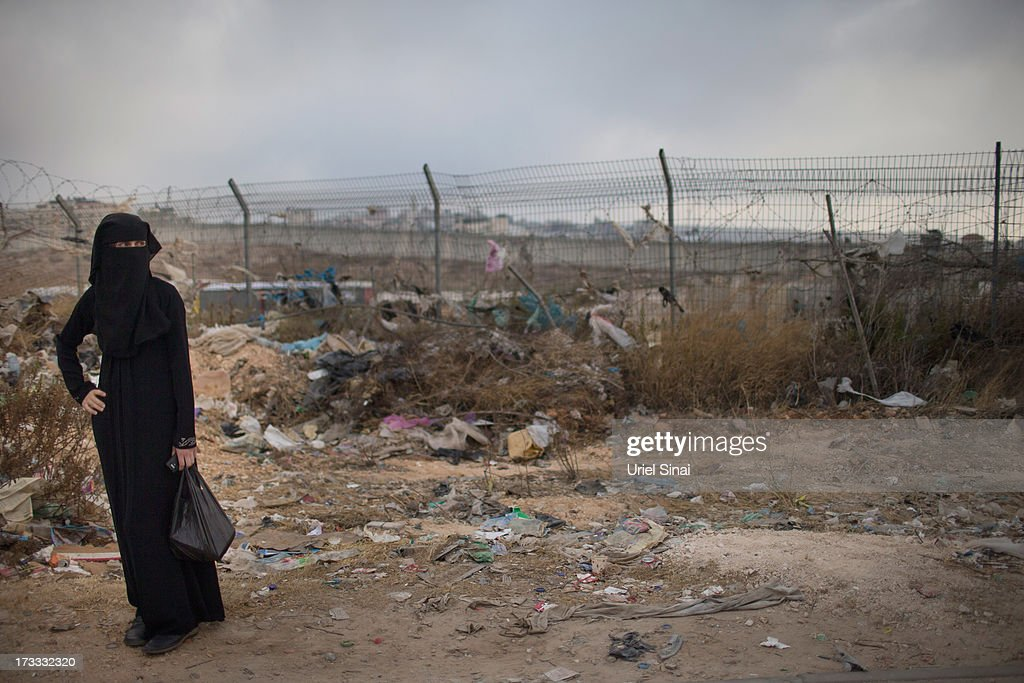 A Palestinian Muslim worshipper stands in front of Israel's separation barrier as worshippers cross the Qalandia checkpoint on their way to Jerusalem on July 12, 2013 near Ramallah, West Bank. Thousands of Palestinian worshippers crossed from the West Bank into Israel to attend the first Friday prayers of Ramadan at the the Al-Aqsa mosque compound in Jerusalem.