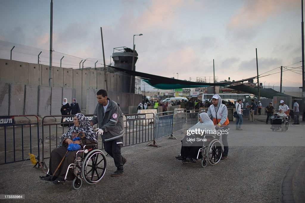 Palestinian Muslim worshippers are helped to cross the Qalandia checkpoint on their way to Jerusalem on July 12, 2013 near Ramallah, West Bank. Thousands of Palestinian worshippers crossed from the West Bank into Israel to attend the first Friday prayers of Ramadan at the the Al-Aqsa mosque compound in Jerusalem.