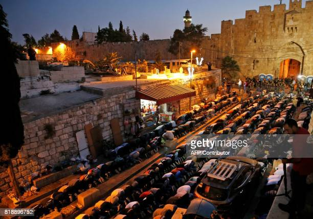 TOPSHOT Palestinian Muslim worshippers pray next to Lions Gate a main entrance to the AlAqsa mosque compound in Jerusalem's Old City on July 19 as...