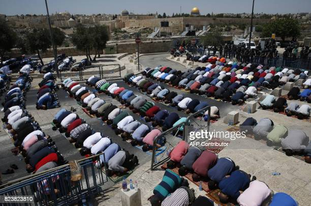 Palestinian Muslim worshippers pray outside Jerusalem's old city overlooking the AlAqsa mosque compound on July 28 2017 Israel barred men under 50...