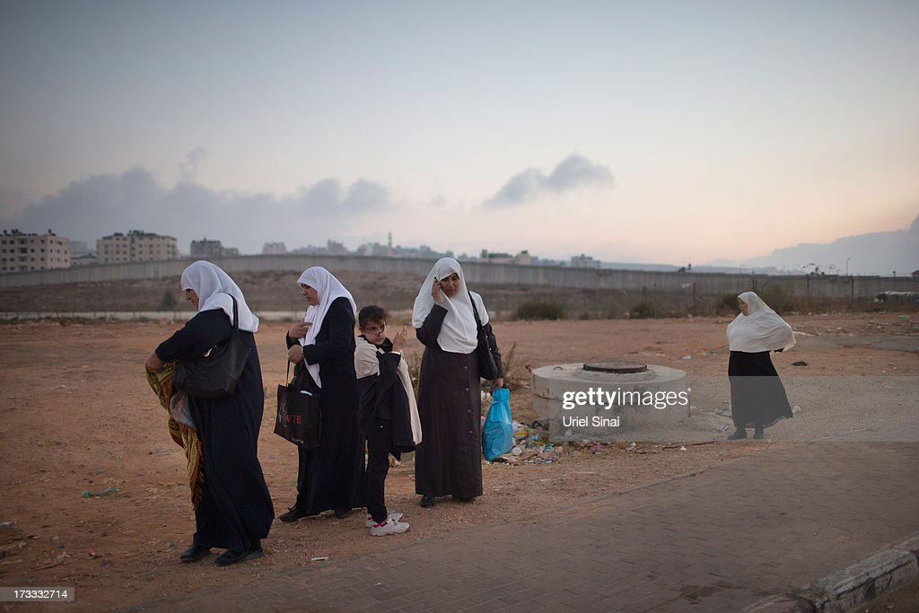 Palestinian Muslim worshippers stand in front of Israel's separation barrier as they cross the Qalandia checkpoint on their way to Jerusalem on July 12, 2013 near Ramallah, West Bank. Thousands of Palestinian worshippers crossed from the West Bank into Israel to attend the first Friday prayers of Ramadan at the the Al-Aqsa mosque compound in Jerusalem.