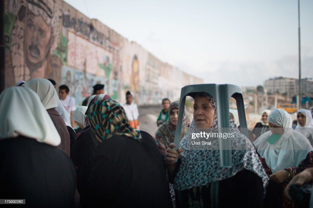 Palestinian Muslim worshippers walk past Israel's separation barrier as they cross the Qalandia checkpoint on their way to Jerusalem on July 12, 2013 near Ramallah, West Bank. Thousands of Palestinian worshippers crossed from the West Bank into Israel to attend the first Friday prayers of Ramadan at the the Al-Aqsa mosque compound in Jerusalem.