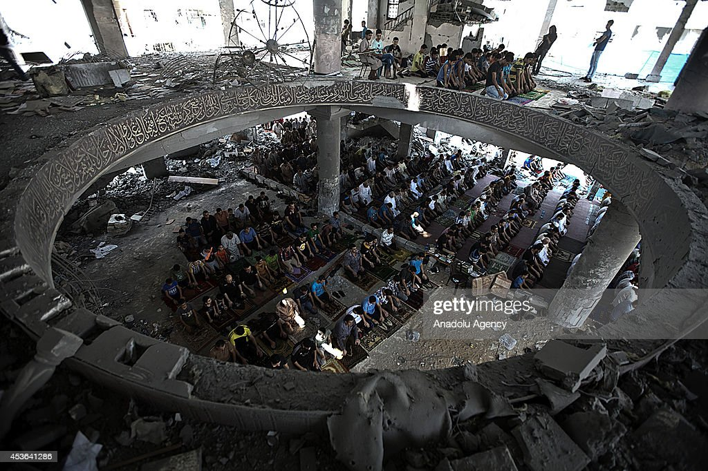 Palestinian Muslims perform Friday Prayer at some parts, remaining standing after Israeli attacks, of Al-Susi Mosque in Gaza City, Gaza on August 15, 2014. According to Palestinian Health Ministry spokesman Palestinian death toll from Israel's weeks-long military onslaught on the Gaza Strip has risen to 1962 and 10,196 others have also been wounded.