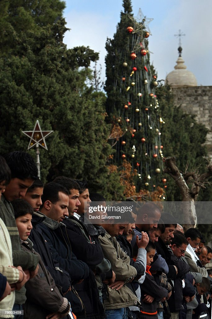 Palestinian Muslims perform their midday Friday prayers in front of the Church of the Nativity and the traditional Christmas tree in Manger Square December 21, 2007 in Bethlehem in the West Bank. The biblical town is celebrating both Christmas and the Muslim Eid al-Adha over the next few days.