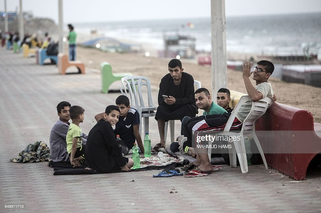 Palestinian Muslims wait to break their fast during the holy fasting month of Ramadan on the the beach in Gaza City on June 27, 2016. / AFP / MAHMUD