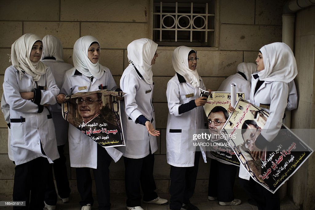 Palestinian nurses hold posters of Maisara Abu Hamdiyeh, a Palestinian prisoner who died of cancer while in Israeli detention, outside Al-Ahli hospital in the West Bank city of Hebron ahead of his funeral on April 4, 2013. The Palestinian leadership has accused Israel of medical negligence, despite moves by the prison service to secure his early release on compassionate grounds, with news of his death sparking angry clashes with the army, notably in Hebron.