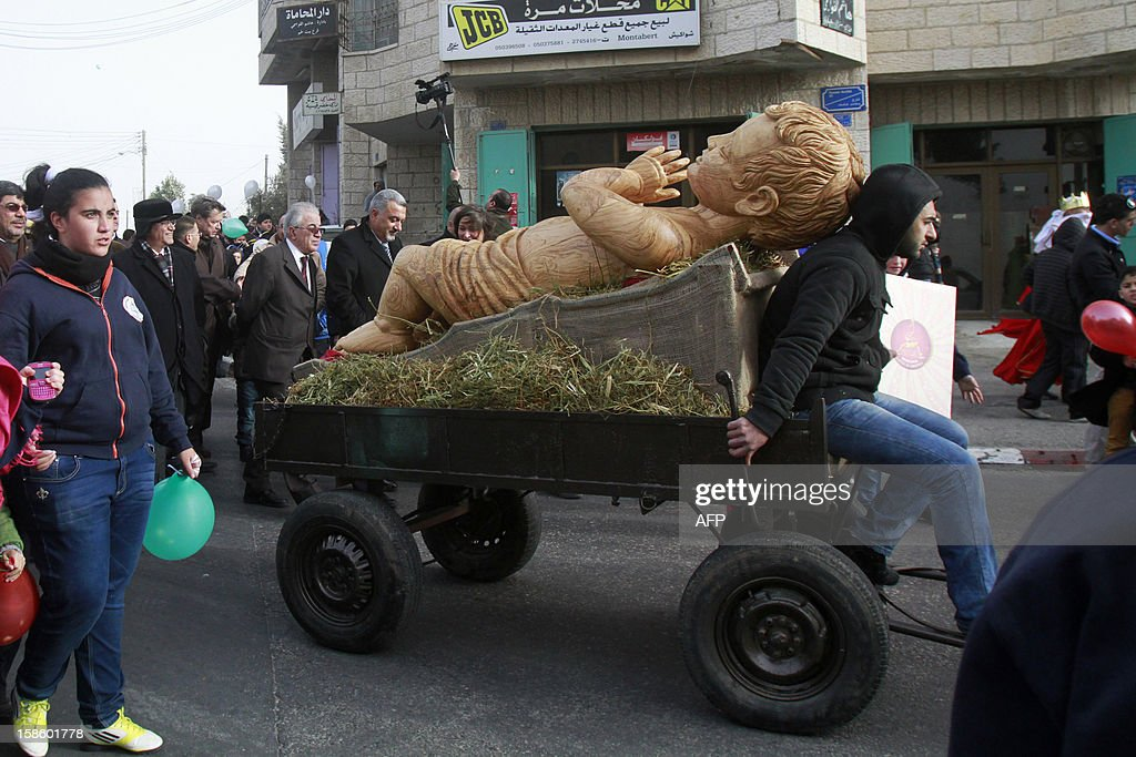 Palestinian officials and members of the clergy follow a kart carrying a wooden carved sculpture of baby Jesus during a march through the West Bank city of Bethlehem on December 20, 2012 ahead of Christmas. The olive wood sculpture weighs about 300 kilos and measures 2,3 metres and is displayed near the Church of the Nativity, believed to be the birthplace of Jesus Christ. AFP PHOTO/MUSA AL SHAER