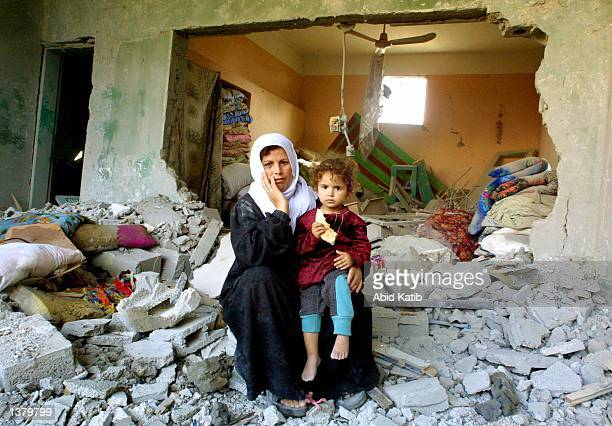 Palestinian Om Hussam Hillis hugs her daughter Rawan as they sit in the rubble of their home September 12 2002 in the village of Al Shejaea in the...