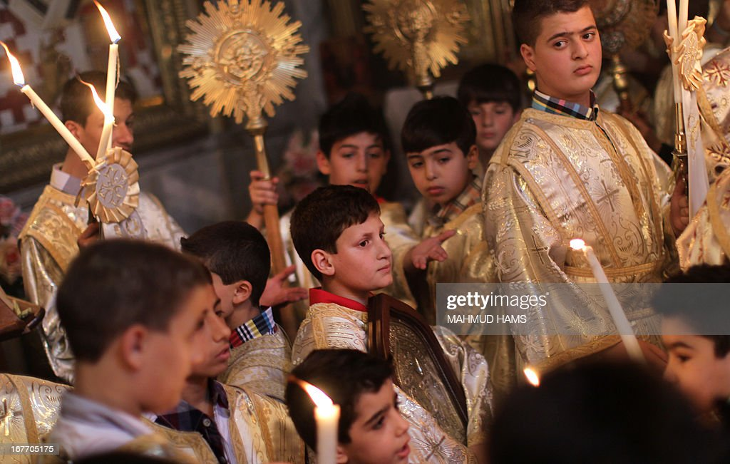 Palestinian Orthodox altar boys attend the Palm Sunday procession in Gaza City on April 28, 2013. Palm Sunday marks the triumphant return of Jesus Christ to Jerusalem when a cheering crowd greeted him waving palm leaves, a week before his crucifixion. Orthodox Christians will celebrate Easter on May 5.