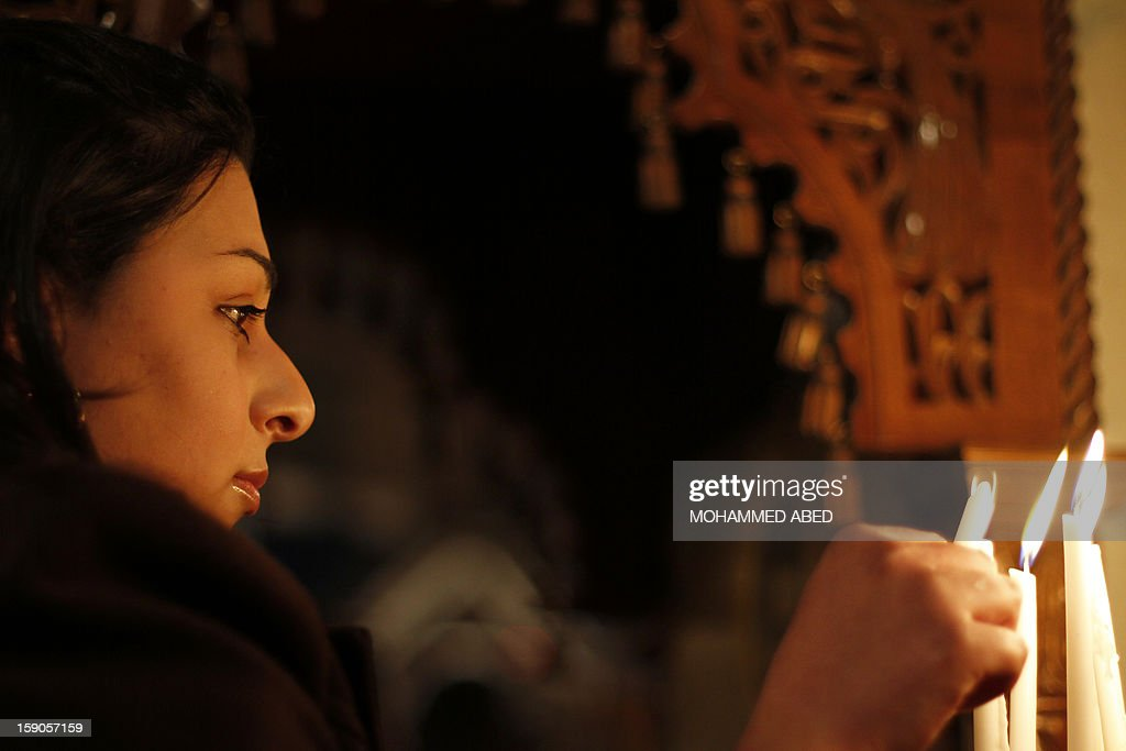 A Palestinian Orthodox Christian woman lights a candle in a church as part of Christmas celebrations on January 7, 2013 in Gaza City. According to the Gregorian calendar, Orthodox Christmas falls 13 days after the December 25 Western feast celebrated in line with the Julian calendar.
