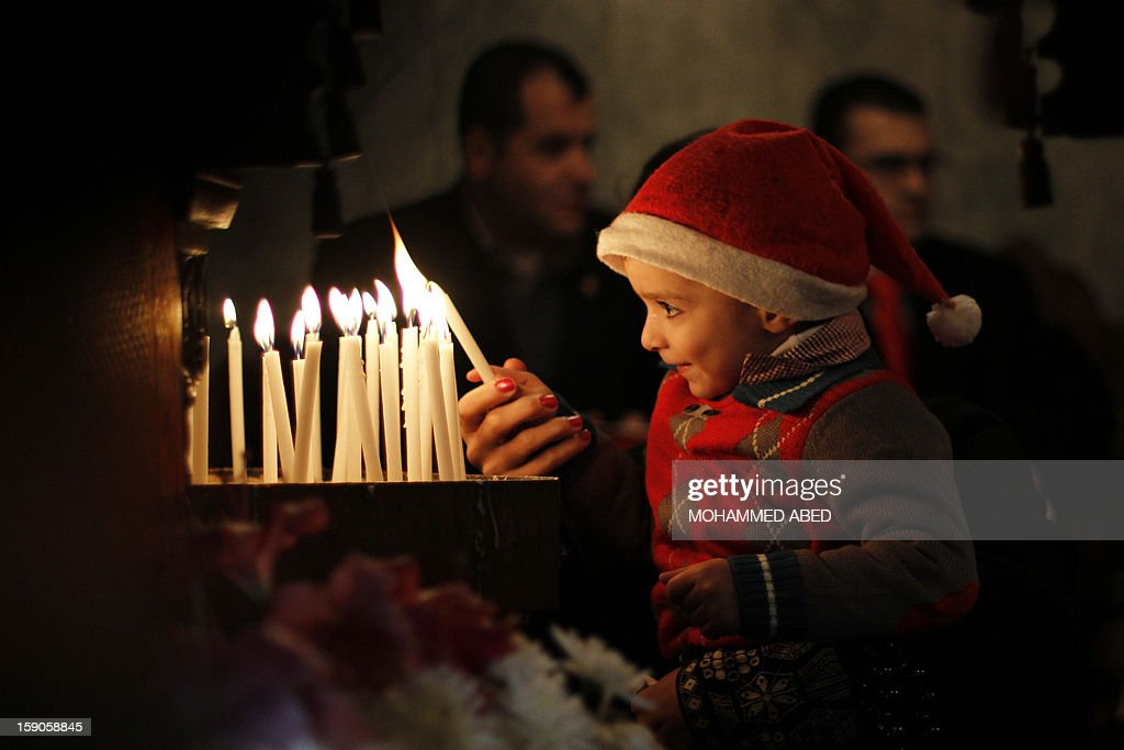 A Palestinian Orthodox Christian young boy his helped to light a candle in the Church of Saint-Porphyrius during Christmas celebrations on January 7, 2013 in Gaza City. According to the Gregorian calendar, Orthodox Christmas falls 13 days after the December 25 Western feast celebrated in line with the Julian calendar. AFP PHOTO/MOHAMMED ABED
