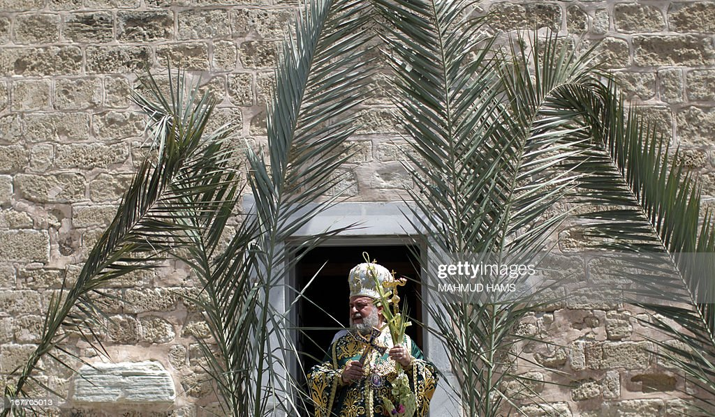 A Palestinian Orthodox priest leads the Palm Sunday procession in Gaza City on April 28, 2013. Palm Sunday marks the triumphant return of Jesus Christ to Jerusalem when a cheering crowd greeted him waving palm leaves, a week before his crucifixion. Orthodox Christians will celebrate Easter on May 5.