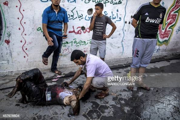 Palestinian paramedic holds the victim of an Israeli air strike at a market place in the Shejaiya neighbourhood near Gaza City on July 30 2014 The...