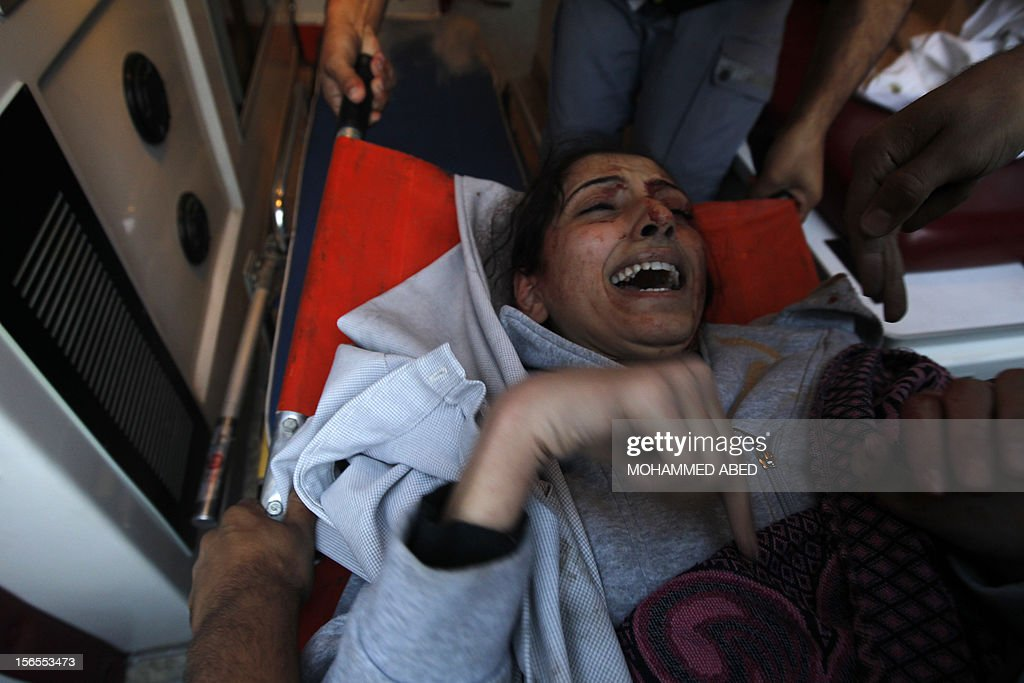 Palestinian paramedics assist an injured woman following an Israeli air raid on a house in Beit Lahia, the northern Gaza Strip on November 17, 2012. Israeli air strikes hit the cabinet headquarters of Gaza's Hamas government, the group said early on November 17, with eyewitnesses reporting extensive damage to the building.
