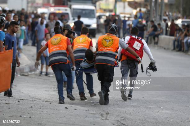 TOPSHOT Palestinian paramedics carry a man injured during clashes between demonstrators and Israeli security forces at the Qalandiya checkpoint...