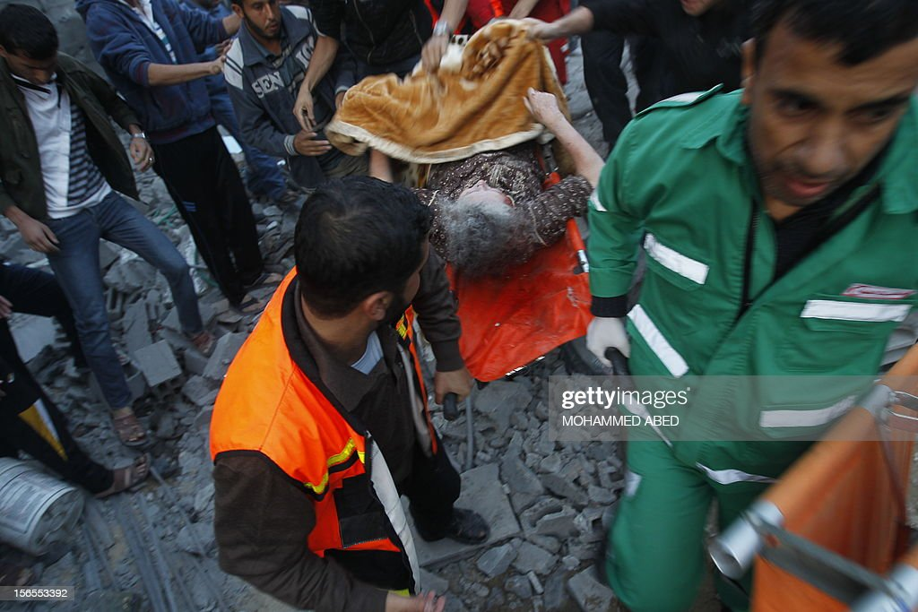 Palestinian paramedics carry an injured woman on a stretcher following an Israeli air raid on a house in Beit Lahia, the northern Gaza Strip on November 17, 2012. Israeli air strikes hit the cabinet headquarters of Gaza's Hamas government, the group said early on November 17, with eyewitnesses reporting extensive damage to the building. AFP PHOTO / MOHAMMED ABED