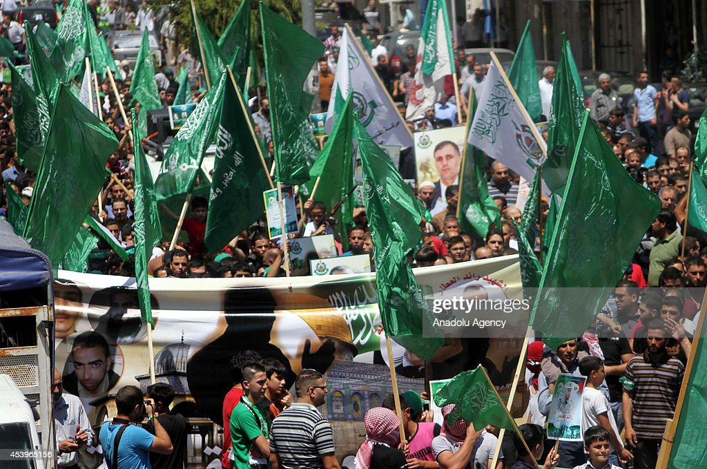 Palestinian people hold Hamas flags during solidarity demonstration staged for people living in Gaza after Friday Prayer in Hebron, West Bank on August 22, 2014.