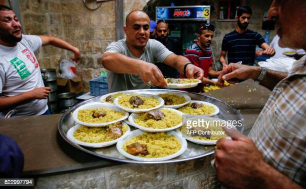 Palestinian place donated food plates on a tray to be distributed to support demonstrators who have kept vigil for over a week as they pray outside...