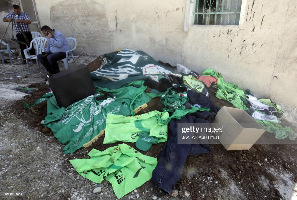 Palestinian plain clothed security gather flags and uniforms said to be used by the Hamas movement and found hidden in underground rooms dug under a house in the West Bank village of Urif, south of the northern city of Nablus on September 23, 2012. Palestinian security believe the tunnels and prison-like cells were dug and built by members of the Hamas movement. AFP PHOTO/JAAFAR ASHTIYEH