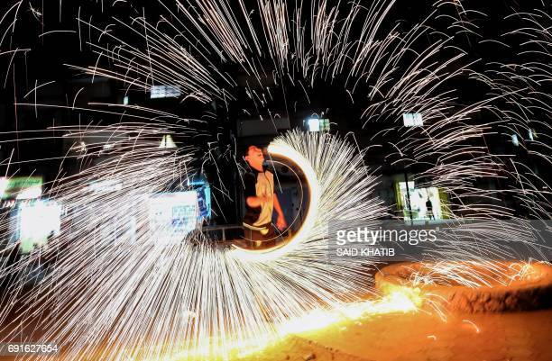 A Palestinian plays with fire crackers as he celebrates the Muslim holy month of Ramadan at the town of Rafah in the southern Gaza Strip on June 2...
