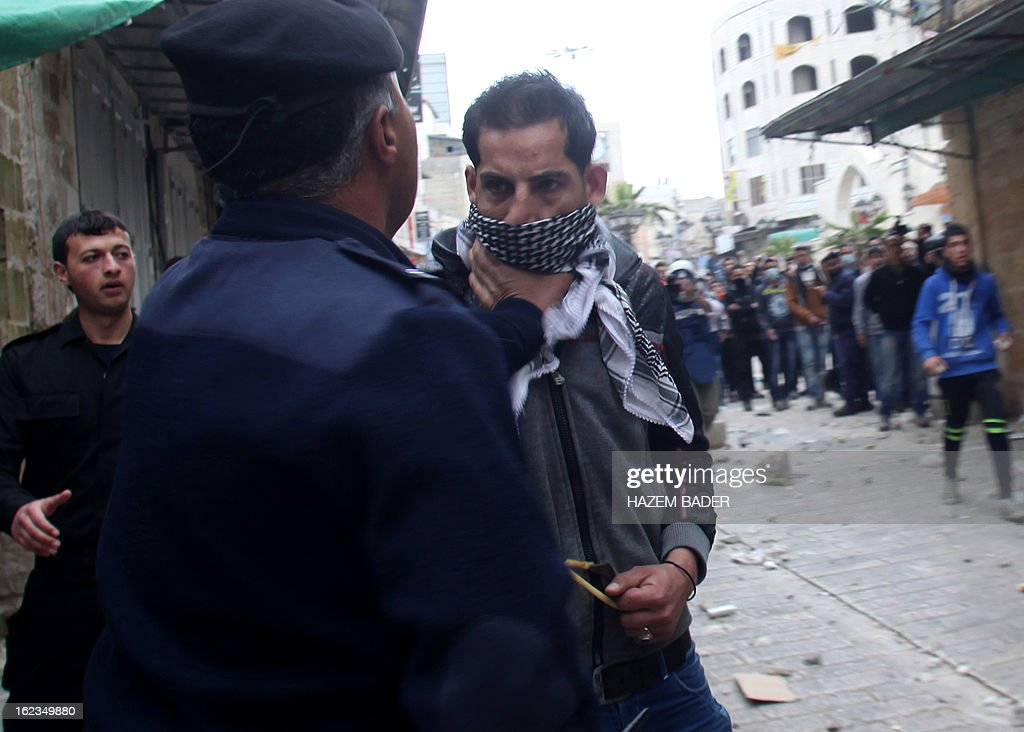 A Palestinian police officer confronts a protestor in an attempt to stop him from hurling stones at Israeli border guards during clashes in al-Shuhada street in the West Bank town of Hebron on February 22, 2013 following a protest demanding the right of access for Palestinians to the street that can only be used by Israeli settlers. AFP PHOTO / HAZEM BADER