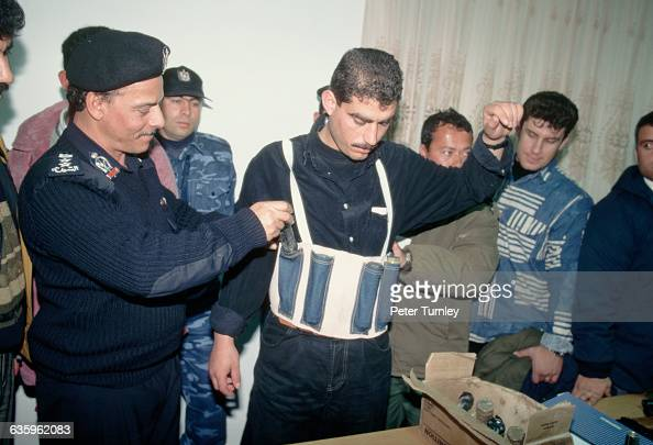 A Palestinian police officer displays a bomb vest and other weapons confiscated during a crackdown against Hamas
