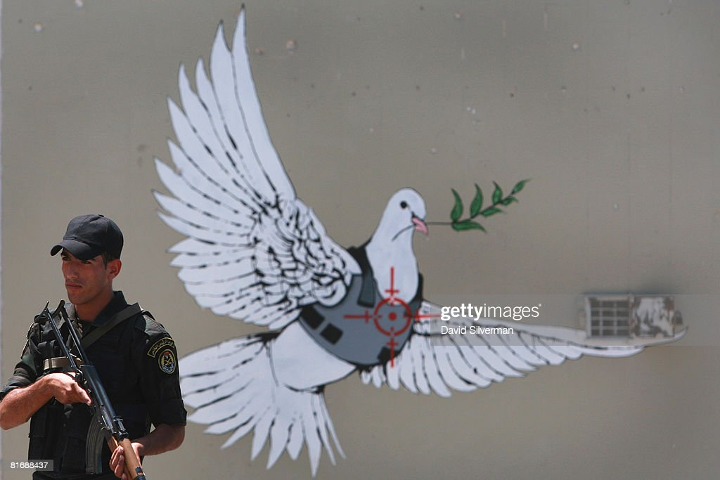 A Palestinian police officer stands guard in front of a mural by the British grafitti artist Banksy as he secures the arrival of French President Nicolas Sarkozy and First Lady Carla Bruni-Sarkozy on June 24, 2008 in Bethlehem, West Bank.