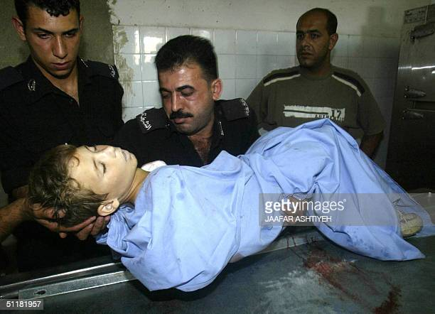 Palestinian police officers carry 17 August 2004 into the morgue the body of 10yearold Palestinian boy Khaled AlOsta who was shot dead during an...
