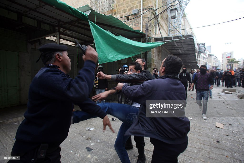 Palestinian police officers confront a protestor in an attempt to stop him from hurling stones at Israeli border guards during clashes in al-Shuhada street in the West Bank town of Hebron on February 22, 2013 following a protest demanding the right of access for Palestinians to the street that can only be used by Israeli settlers. AFP PHOTO / HAZEM BADER
