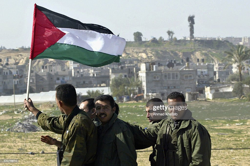 Palestinian police officers wave a Palestinian flag outside their baseas they deploy outside the Rafah refugee camp adjacent to the Israeli...