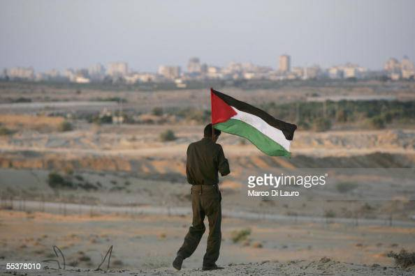 Palestinian p[oliceman holds a Palestinian flag while waiting for the Israeli Army to withdraw from the the Netzarim Settlement September 11 2005 in...