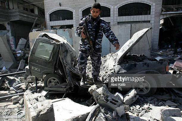 Palestinian policeman inspects the damage after an Israeli airstrike on a building belonging to the Hamas Government's interior Ministry which...