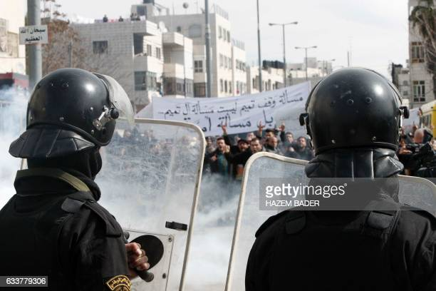 TOPSHOT Palestinian policemen stand opposite to demonstrators during a protest against a decision by the Palestinian Authority to grant a public land...