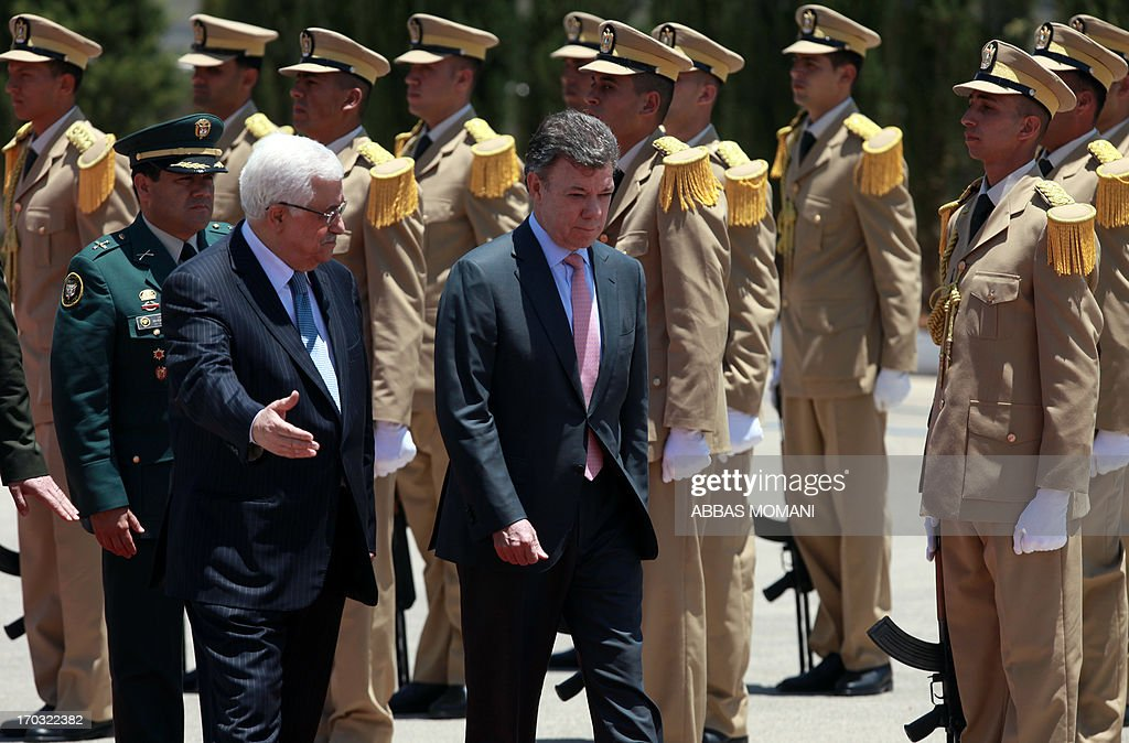 Palestinian president Mahmoud Abbas (L) and his Colombian counterpart Juan Manuel Santos (C) review the honour guard during a welcome ceremony in the West Bank city of Ramallah on June 11, 2013 as the latter continues his official visit to the region. AFP PHOTO/ABBAS MOMANI