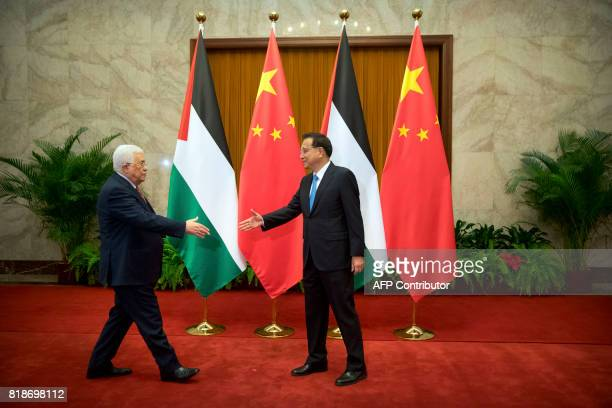 Palestinian President Mahmoud Abbas prepares to shake hands with Chinese Premier Li Keqiang as he arrives for a meeting at the Great Hall of the...