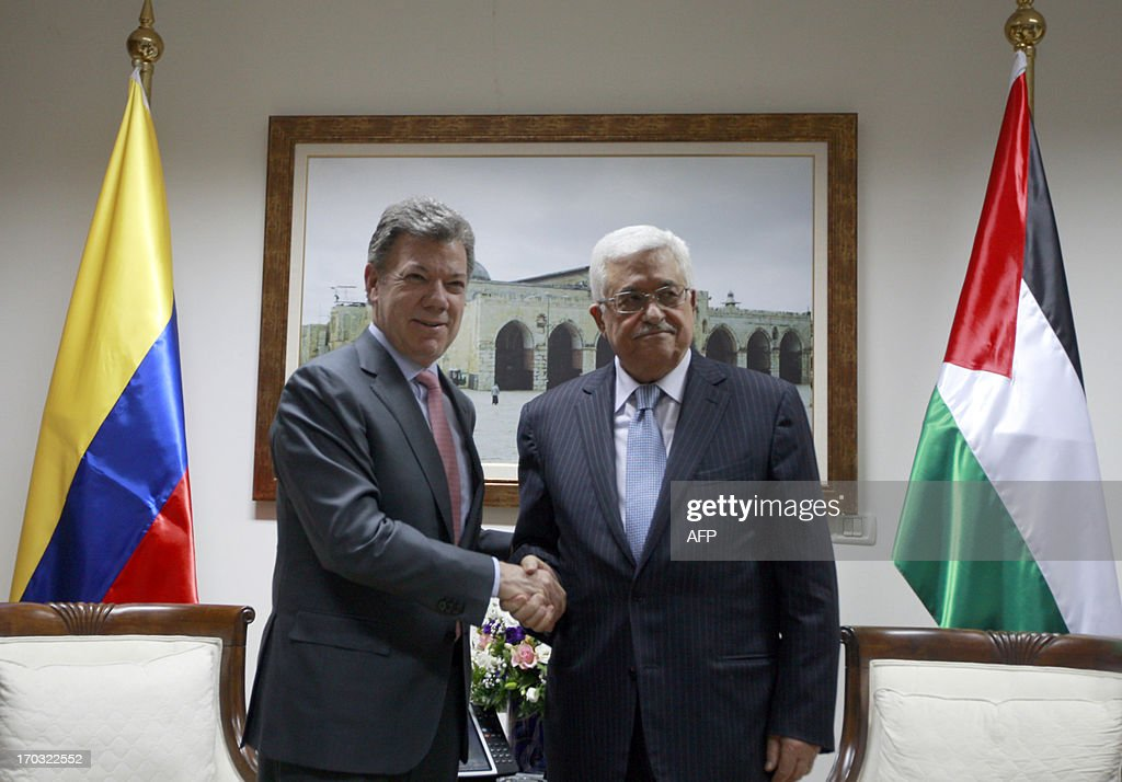 Palestinian president Mahmoud Abbas (R) shakes hands with his Colombian counterpart Juan Manuel Santos (L) following the latter's arrival in the West Bank city of Ramallah on June 11, 2013 during part of his official visit to the region. AFP PHOTO/POOL/MAJDI MOHAMMED