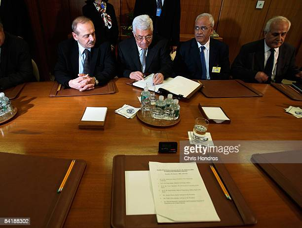 Palestinian President Mahmoud Abbas signs a guest book surrounded by his entourage before a meeting with UN Secretary General Ban KiMoon at the...