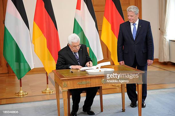 Palestinian President Mahmoud Abbas signs the official guest book as German President Joachim Gauck looks on during their meeting at Bellevue Palace...
