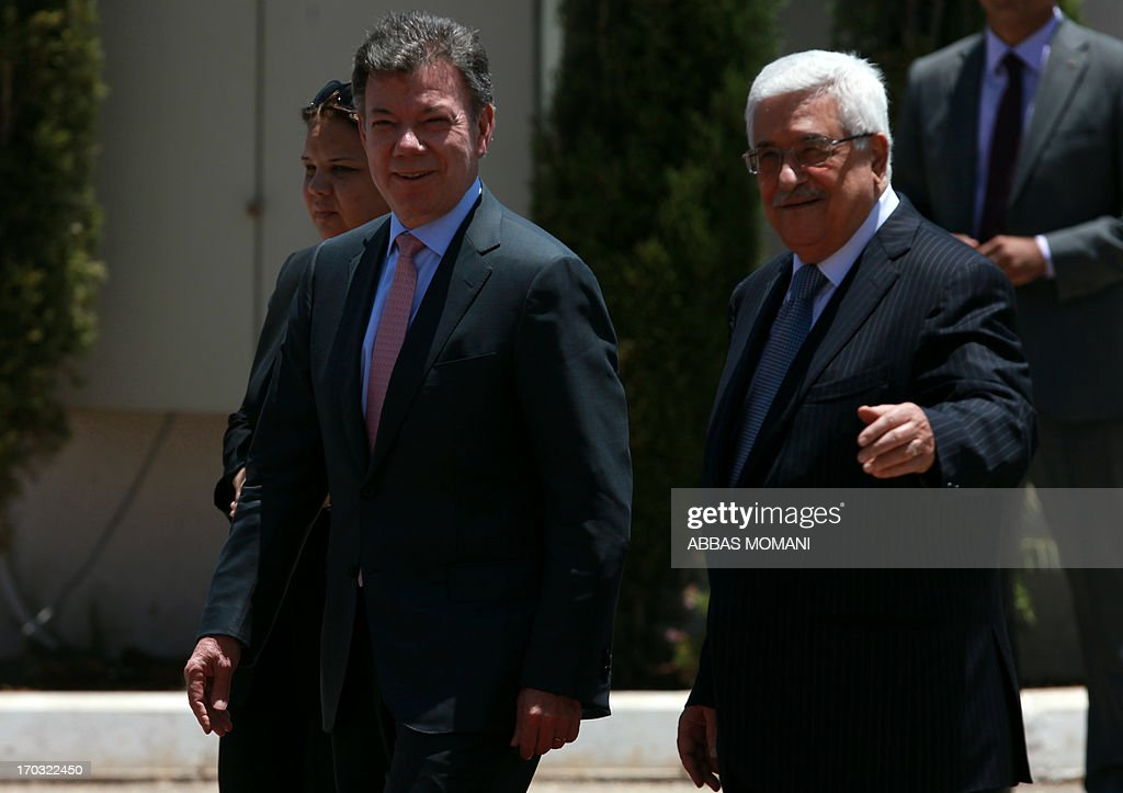Palestinian president Mahmoud Abbas (R) welcomes his Colombian counterpart Juan Manuel Santos (C) as they review the honour guard during a ceremony in the West Bank city of Ramallah on June 11, 2013. Santos is on an official visit to the region. AFP PHOTO/ABBAS MOMANI