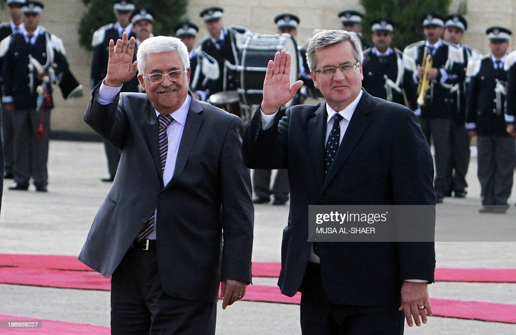 Palestinian president Mahmud Abbas (L) and President of Poland, Bronislaw Komorowski wave during a welcome ceremony ahead of a meeting in the West Bank city of Bethlehem on November 5, 2013. AFP PHOTO / MUSA AL-SHAER