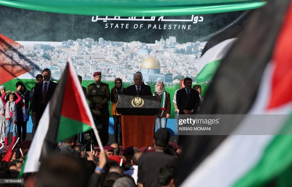 Palestinian president Mahmud Abbas (C) delivers a speech to the crowd waving their national flag, upon his arrival in the West Bank city of Ramallah on December 2, 2012, after winning upgraded United Nations status for the Palestinians earlier in the week. Abbas said 'Palestine has accomplished a historic achievement at the UN,' three days after the United Nations General Assembly granted the Palestinians non-member state observer status in a 138-9 vote.