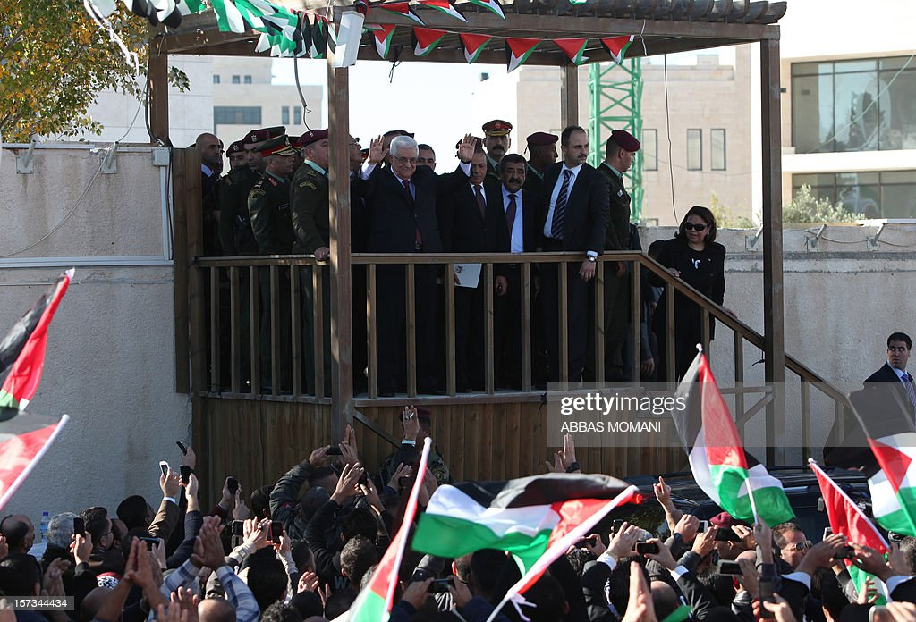 Palestinian president Mahmud Abbas (C) greets the crowd waving their national flag upon his arrival in the West Bank city of Ramallah on December 2, 2012, after winning upgraded United Nations status for the Palestinians. Abbas said 'Palestine has accomplished a historic achievement at the UN,' three days after the United Nations General Assembly granted the Palestinians non-member state observer status in a 138-9 vote. AFP PHOTO / ABBAS MOMANI