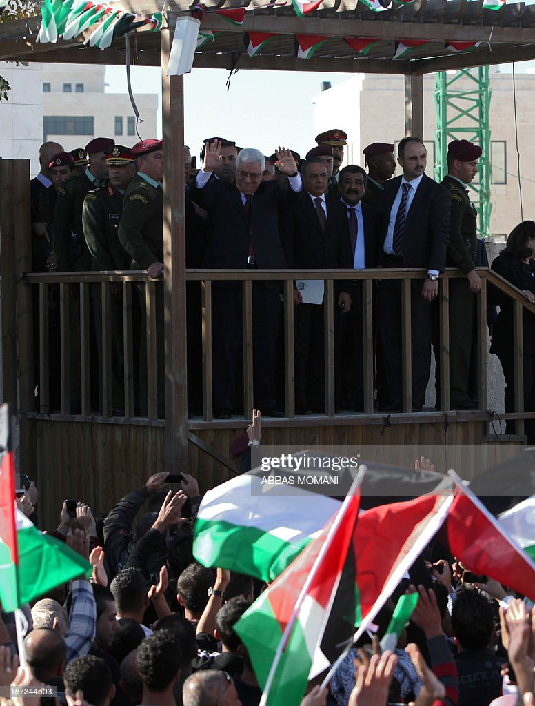 Palestinian president Mahmud Abbas (C) greets the crowd waving their national flag, upon his arrival in the West Bank city of Ramallah on December 2, 2012, after winning upgraded United Nations status for the Palestinians earlier in the week. Abbas said 'Palestine has accomplished a historic achievement at the UN,' three days after the United Nations General Assembly granted the Palestinians non-member state observer status in a 138-9 vote. AFP PHOTO / ABBAS MOMANI